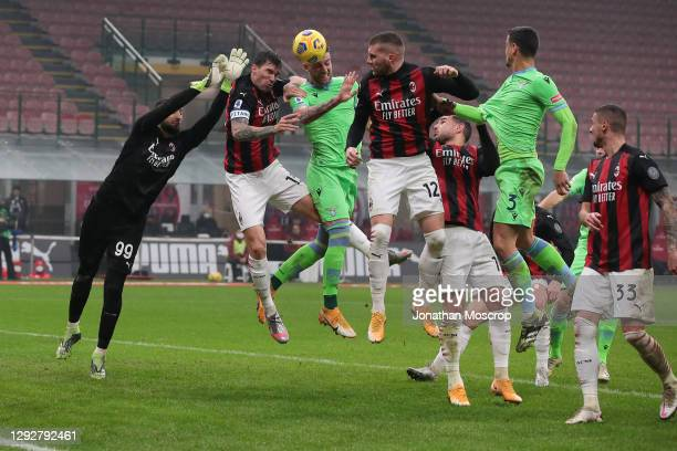 Gianluigi Donnarumma of AC Milan jumps for a ball with team mates Alessio Romagnoli and Ante Rebic along with Sergej Milinkovic-Savic of SS Lazio...