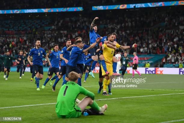 Gianluigi Donnarumma of Italy celebrates with teammates after saving the England fifth penalty taken by Bukayo Saka of England in a penalty shoot out...
