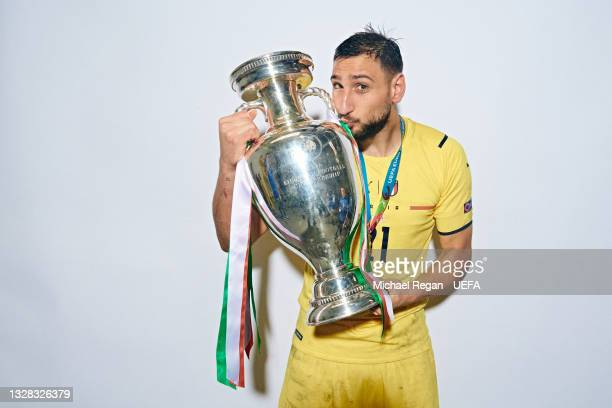 Gianluigi Donnarumma of Italy poses with The Henri Delaunay Trophy during an Italy Portrait Session following their side's victory in the UEFA Euro...