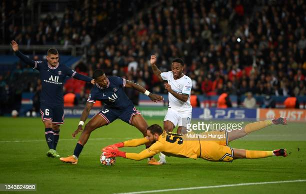 Gianluigi Donnarumma of Paris Saint-Germain stretches for the ball whilst under pressure from Raheem Sterling of Manchester City during the UEFA...