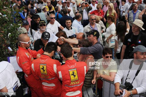 Gianmaria Bruni of Italy Pierre Kaffer of Germany and Jaime Melo of Brazil and drivers of the Risi Competizione Ferrari 430 GT sign autographs during...