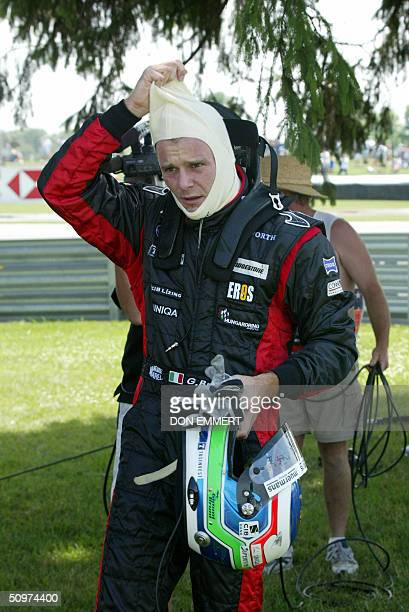 Gianmaria Bruni of Italy walks back to the pits after stalling his car during practice 18 June at the US Grand Prix at the Indianapolis Motor...