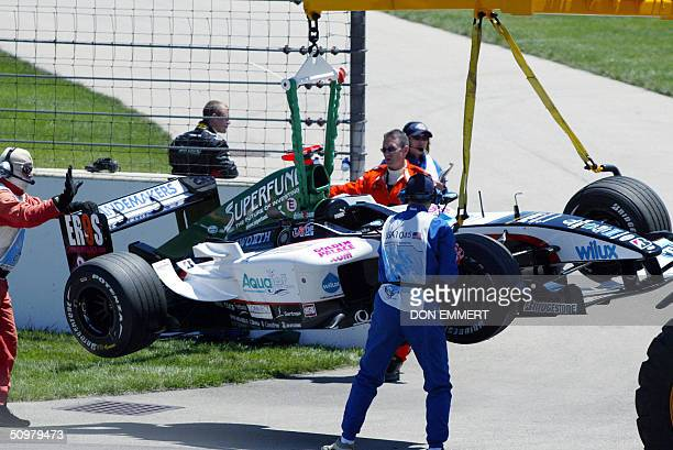 Gianmaria Bruni of Italy watches as his car is lifted off the track 20 June 2004 at the US Grand Prix at the Indianapolis Motor Speedway in...