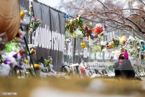 Gianna Giorlando sits next to a makeshift memorial for the victims of a mass shooting outside a King Soopers grocery store on March 24, 2021 in...
