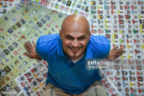 Gianni Bellini, owner of the largest Panini football stickers collection in the world, poses for a picture with collectable stickers by Panini in his...