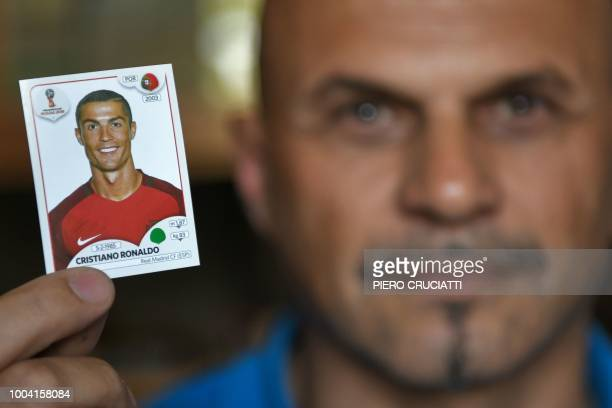 Gianni Bellini owner of the largest Panini football stickers collection in the world poses for a picture holding a Cristiano Ronaldo collectible card...