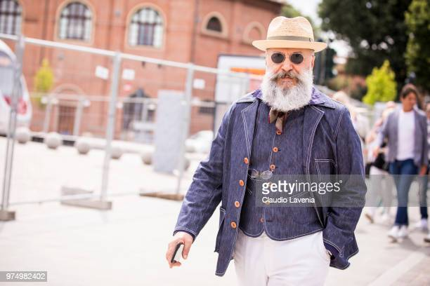 Gianni Fontana wearing straw hat denim blazer and vest and white trousers is seen during the 94th Pitti Immagine Uomo at Fortezza Da Basso on June 14...