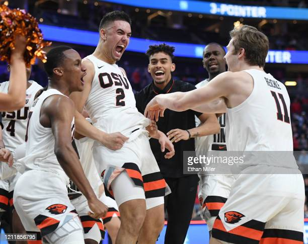 Gianni Hunt, Jarod Lucas and Zach Reichle of the Oregon State Beavers celebrate after Lucas hit a game-winning 3-pointer against the Utah Utes during...