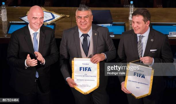 Gianni Infantino president of FIFA Claudio Chiqui Tapia president of AFA and Alejandro Dominguez of CONMEBOL pose after a press conference at AFA as...