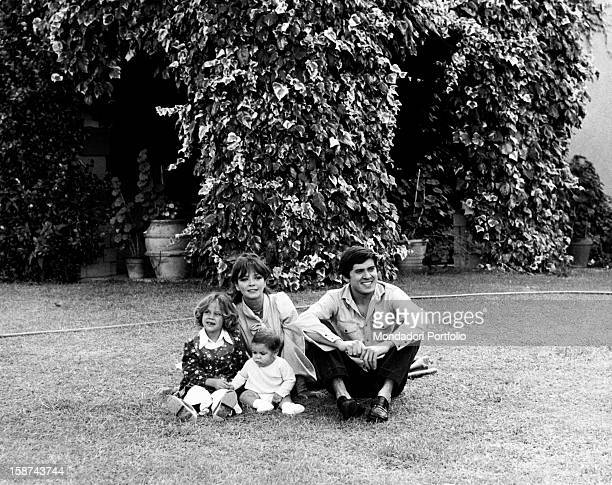 Gianni Morandi with his wife, the actress Laura Efrikian and their children and their children Marianna and Marco, sitting in the garden. Rome, 1974.