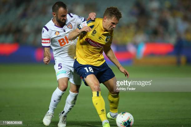 Gianni Stensess of the Central Coast Mariners contests the ball against Ivan Franjic of Perth Glory during the round 12 A-League match between the...
