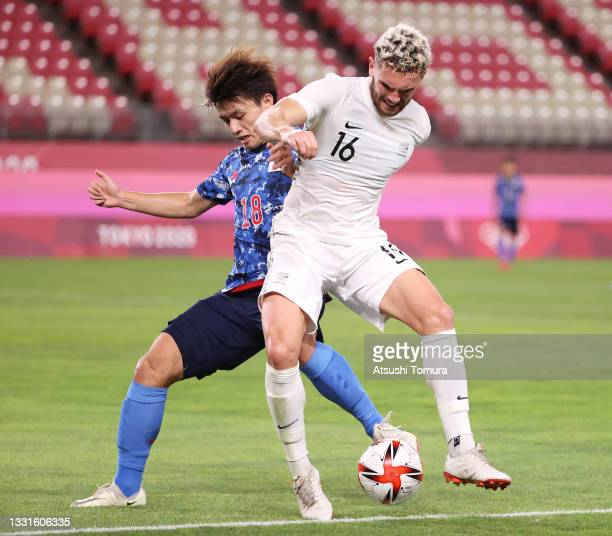 Gianni Stensness of Team New Zealand battles for possession with Ayase Ueda of Team Japan during the Men's Quarter Final match between Japan and New...