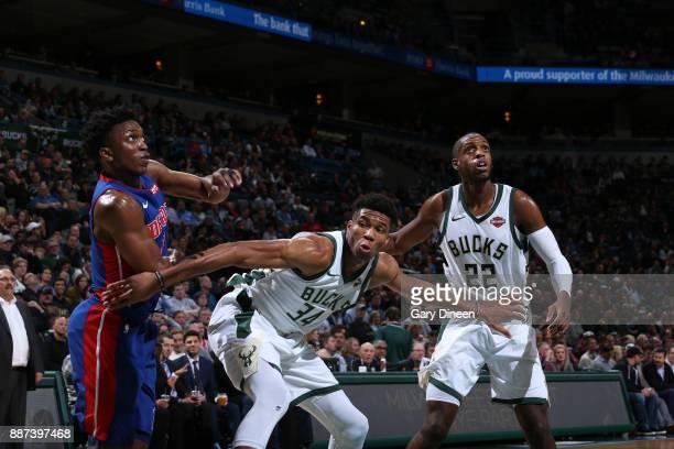 Giannis Antetokounmpo and Khris Middleton of the Milwaukee Bucks plays defense against Stanley Johnson of the Detroit Pistons on December 6 2017 at...