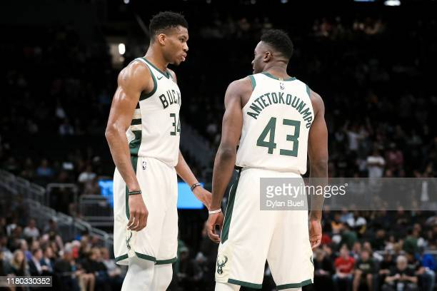 Giannis Antetokounmpo and Thanasis Antetokounmpo of the Milwaukee Bucks meet in the second quarter against the Utah Jazz during a preseason game at...