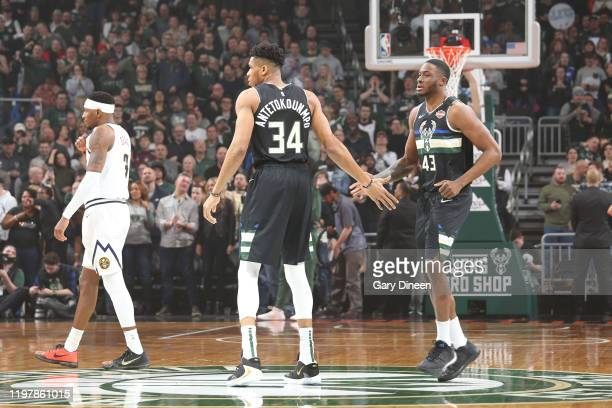 Giannis Antetokounmpo and Thanasis Antetokounmpo of the Milwaukee Bucks hifive during the game against the Denver Nuggets on January 31 2020 at the...