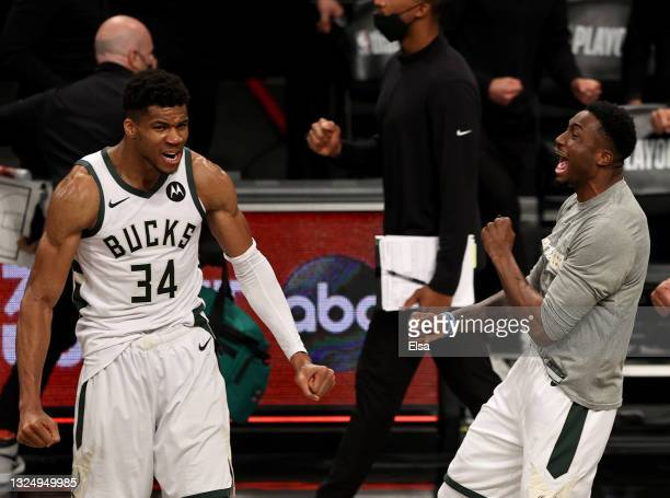 Giannis Antetokounmpo and Thanasis Antetokounmpo of the Milwaukee Bucks celebrate the win of game seven of the Eastern Conference second round at...