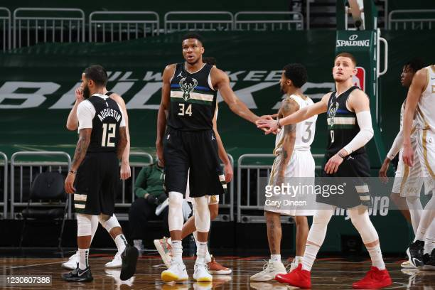 Giannis Antetokounmpo hi-fives Donte DiVincenzo of the Milwaukee Bucks during the game against the Dallas Mavericks on January 15, 2021 at the Fiserv...