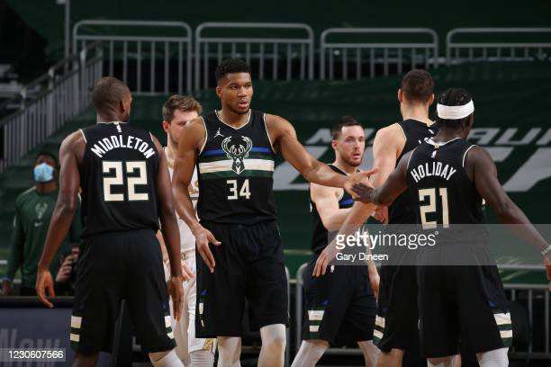 Giannis Antetokounmpo hi-fives Jrue Holiday of the Milwaukee Bucks during the game against the Dallas Mavericks on January 15, 2021 at the Fiserv...