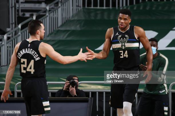 Giannis Antetokounmpo hi-fives Pat Connaughton of the Milwaukee Bucks during the game against the Dallas Mavericks on January 15, 2021 at the Fiserv...