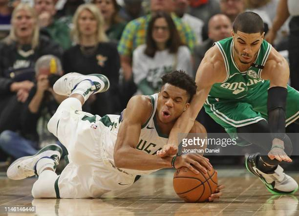 Giannis Antetokounmpo of the Milwaukee Bucks and Jayson Tatum of the Boston Celtics dives for a loose ball at Fiserv Forum on April 30 2019 in...