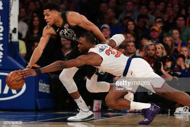 Giannis Antetokounmpo of the Milwaukee Bucks and Noah Vonleh of the New York Knicks fight for the ball during the fourth quarter of the game at...