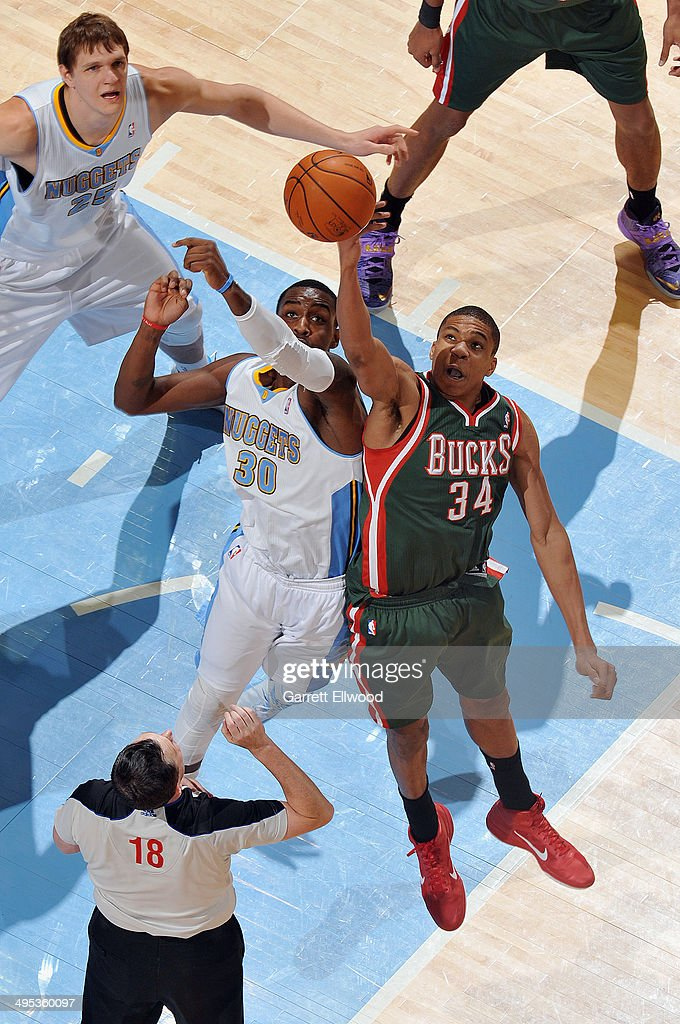 Giannis Antetokounmpo #34 of the Milwaukee Bucks and Quincy Miller #30 of the Denver Nuggets jump for the ball during the game on February 5, 2014 at the Pepsi Center in Denver, Colorado.