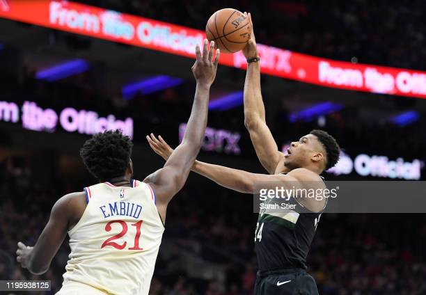 Giannis Antetokounmpo of the Milwaukee Bucks attempts a basket as Joel Embiid of the Philadelphia 76ers defends during the first half of the game at...