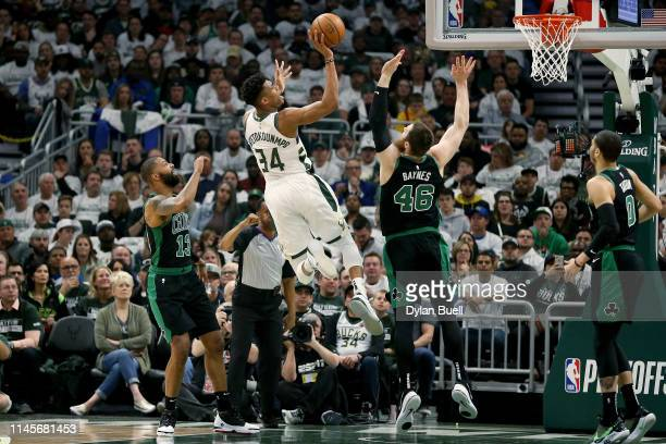Giannis Antetokounmpo of the Milwaukee Bucks attempts a shot while being guarded by Marcus Morris and Aron Baynes of the Boston Celtics in the first...