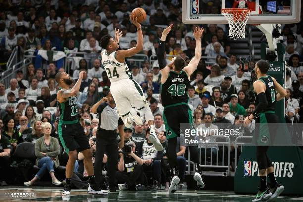 Giannis Antetokounmpo of the Milwaukee Bucks attempts a shot while being guarded by Aron Baynes of the Boston Celtics in the first quarter during...
