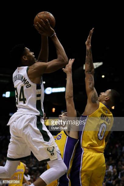 Giannis Antetokounmpo of the Milwaukee Bucks attempts a shot while being guarded by Lonzo Ball and Kyle Kuzma of the Los Angeles Lakers in the first...