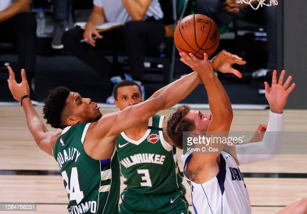 Giannis Antetokounmpo of the Milwaukee Bucks blocks a shot by Luka Doncic of the Dallas Mavericks as George Hill of the Milwaukee Bucks looks on at...