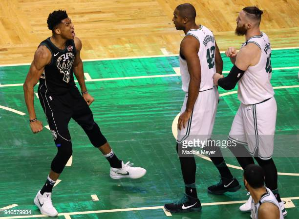 Giannis Antetokounmpo of the Milwaukee Bucks celebrates in front of Al Horford of the Boston Celtics and Aron Baynes during the first quarter of Game...
