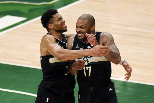 Giannis Antetokounmpo of the Milwaukee Bucks celebrates with teammate P.J. Tucker in the final seconds before defeating the Phoenix Suns in Game Six...