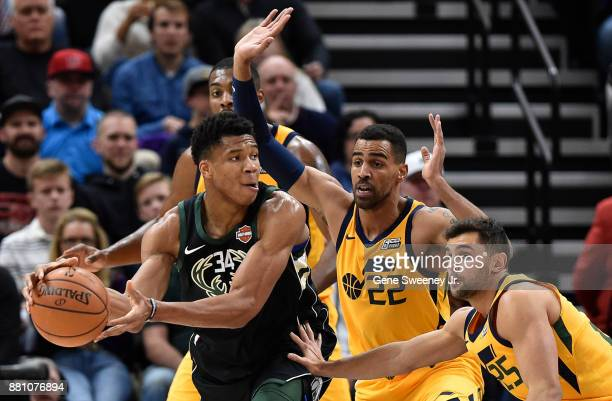 Giannis Antetokounmpo of the Milwaukee Bucks controls the ball while being guarded by Thabo Sefolosha of the Utah Jazz and teammate Raul Neto during...