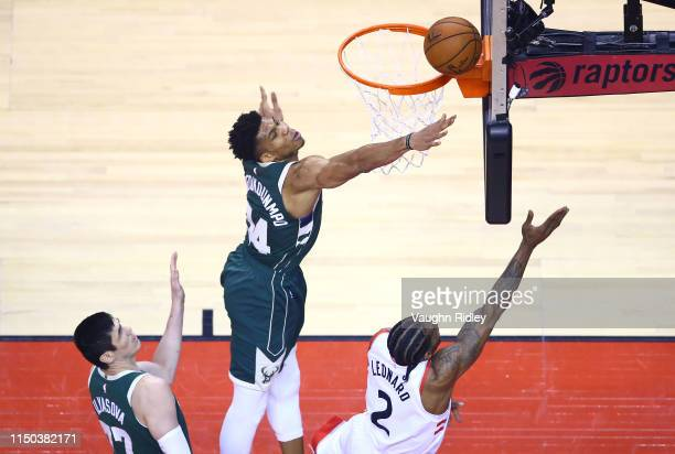 Giannis Antetokounmpo of the Milwaukee Bucks defends a shot by Kawhi Leonard of the Toronto Raptors during the first half in game three of the NBA...
