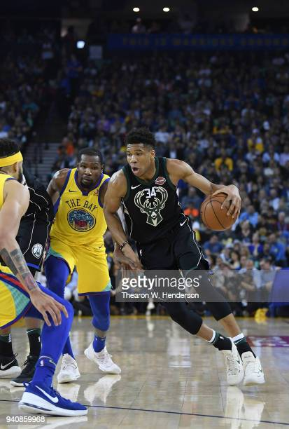 Giannis Antetokounmpo of the Milwaukee Bucks dribbles the ball past Kevin Durant of the Golden State Warriors during an NBA basketball game at ORACLE...