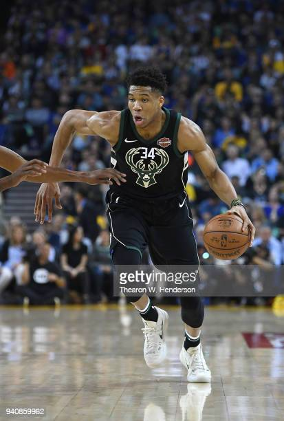 Giannis Antetokounmpo of the Milwaukee Bucks dribbles the ball against the Golden State Warriors during an NBA basketball game at ORACLE Arena on...