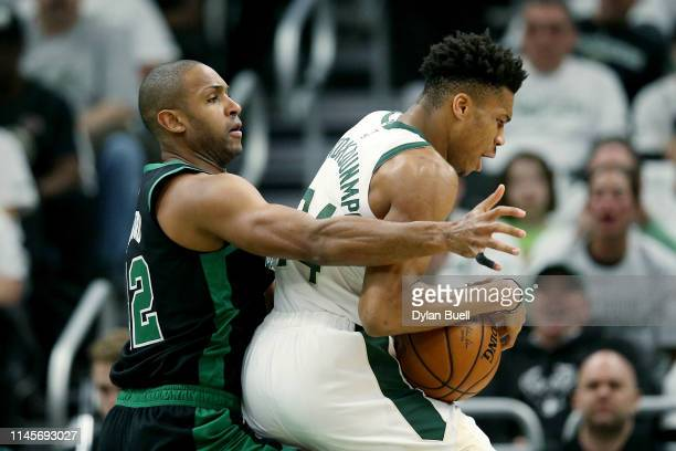 Giannis Antetokounmpo of the Milwaukee Bucks dribbles the ball while being guarded by Al Horford of the Boston Celtics in the first quarter during...