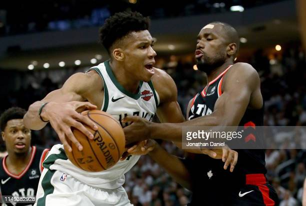 Giannis Antetokounmpo of the Milwaukee Bucks dribbles the ball while being guarded by Serge Ibaka of the Toronto Raptors in the third quarter in Game...