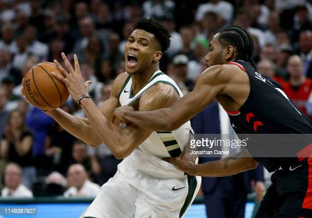 Giannis Antetokounmpo of the Milwaukee Bucks dribbles the ball while being guarded by Kawhi Leonard of the Toronto Raptors in the fourth quarter in...