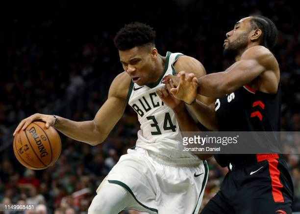 Giannis Antetokounmpo of the Milwaukee Bucks dribbles the ball while being guarded by Kawhi Leonard of the Toronto Raptors in the fourth quarter...