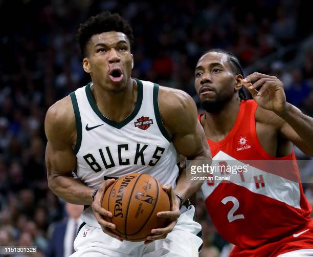 Giannis Antetokounmpo of the Milwaukee Bucks dribbles the ball while being guarded by Kawhi Leonard of the Toronto Raptors in the third quarter...