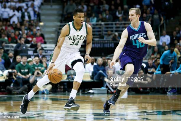 Giannis Antetokounmpo of the Milwaukee Bucks dribbles the ball while being guarded by Cody Zeller of the Charlotte Hornets in the first quarter at...
