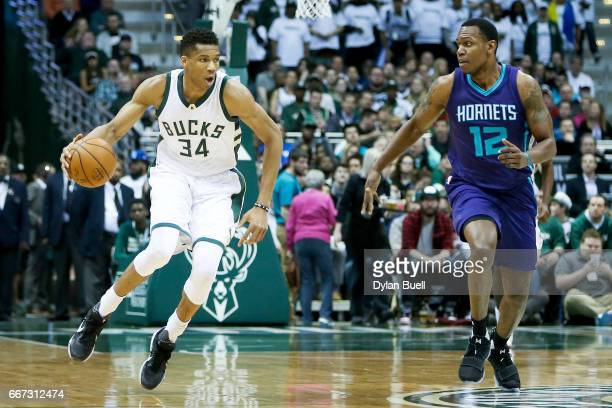Giannis Antetokounmpo of the Milwaukee Bucks dribbles the ball while being guarded by Treveon Graham of the Charlotte Hornets in the second quarter...