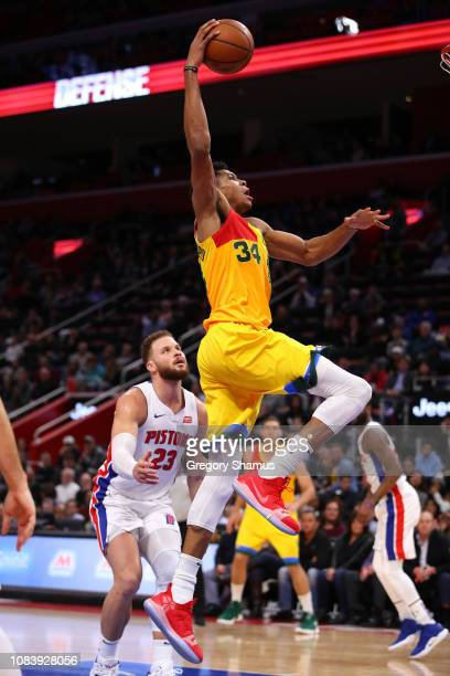 Giannis Antetokounmpo of the Milwaukee Bucks drives for a dunk past Blake Griffen of the Detroit Pistons at Little Caesars Arena on December 17 2018...