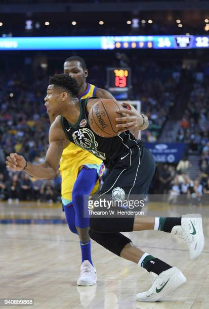 Giannis Antetokounmpo of the Milwaukee Bucks drives on Kevin Durant of the Golden State Warriors during an NBA basketball game at ORACLE Arena on...