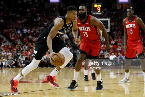Giannis Antetokounmpo of the Milwaukee Bucks drives to the basket defended by James Harden of the Houston Rockets in the first half at Toyota Center...