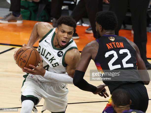 Giannis Antetokounmpo of the Milwaukee Bucks drives to the basket against against Deandre Ayton of the Phoenix Suns during the second half in Game...