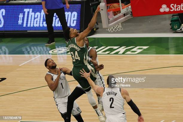 Giannis Antetokounmpo of the Milwaukee Bucks dunks against Blake Griffin of the Brooklyn Nets during the first half of Game Three of the Eastern...