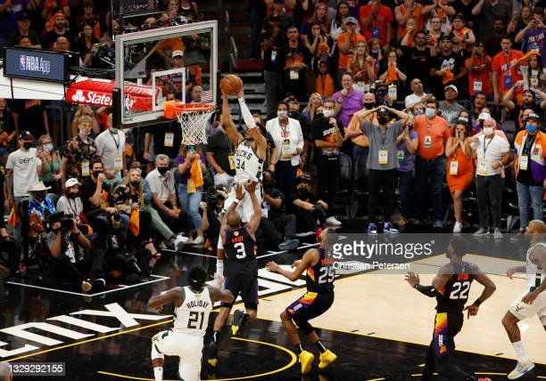 Giannis Antetokounmpo of the Milwaukee Bucks dunks against Chris Paul of the Phoenix Suns during the second half in Game Five of the NBA Finals at...